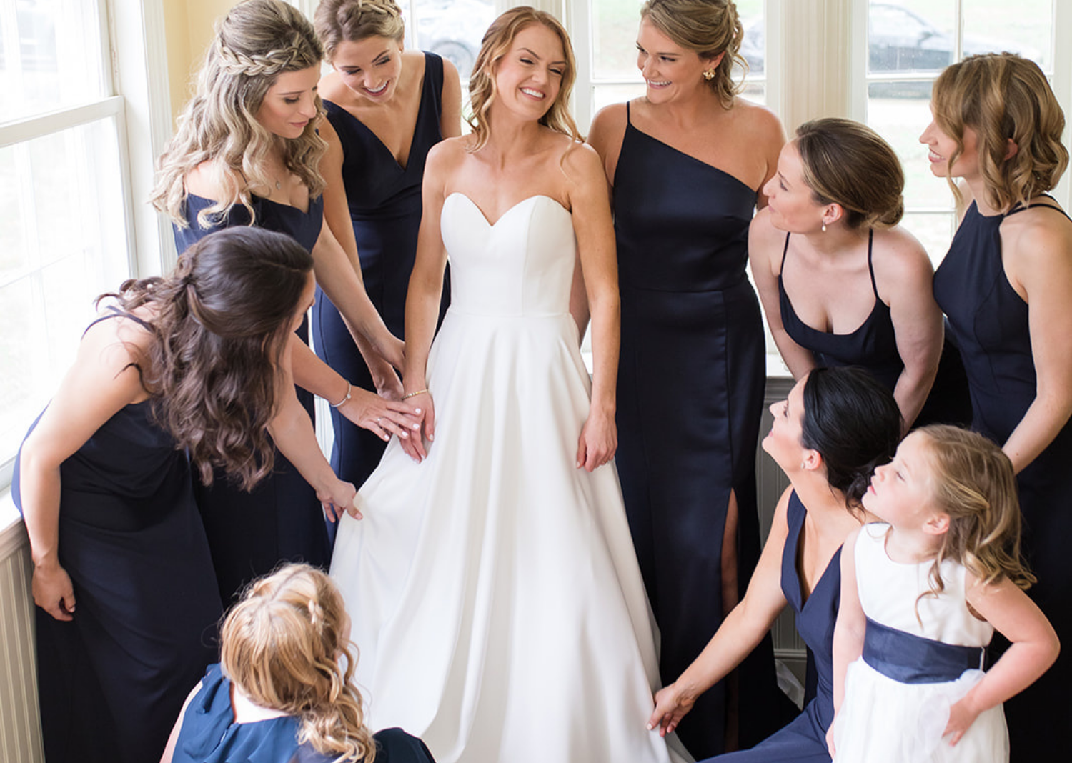 bridesmaids looking at the bride in her wedding dress