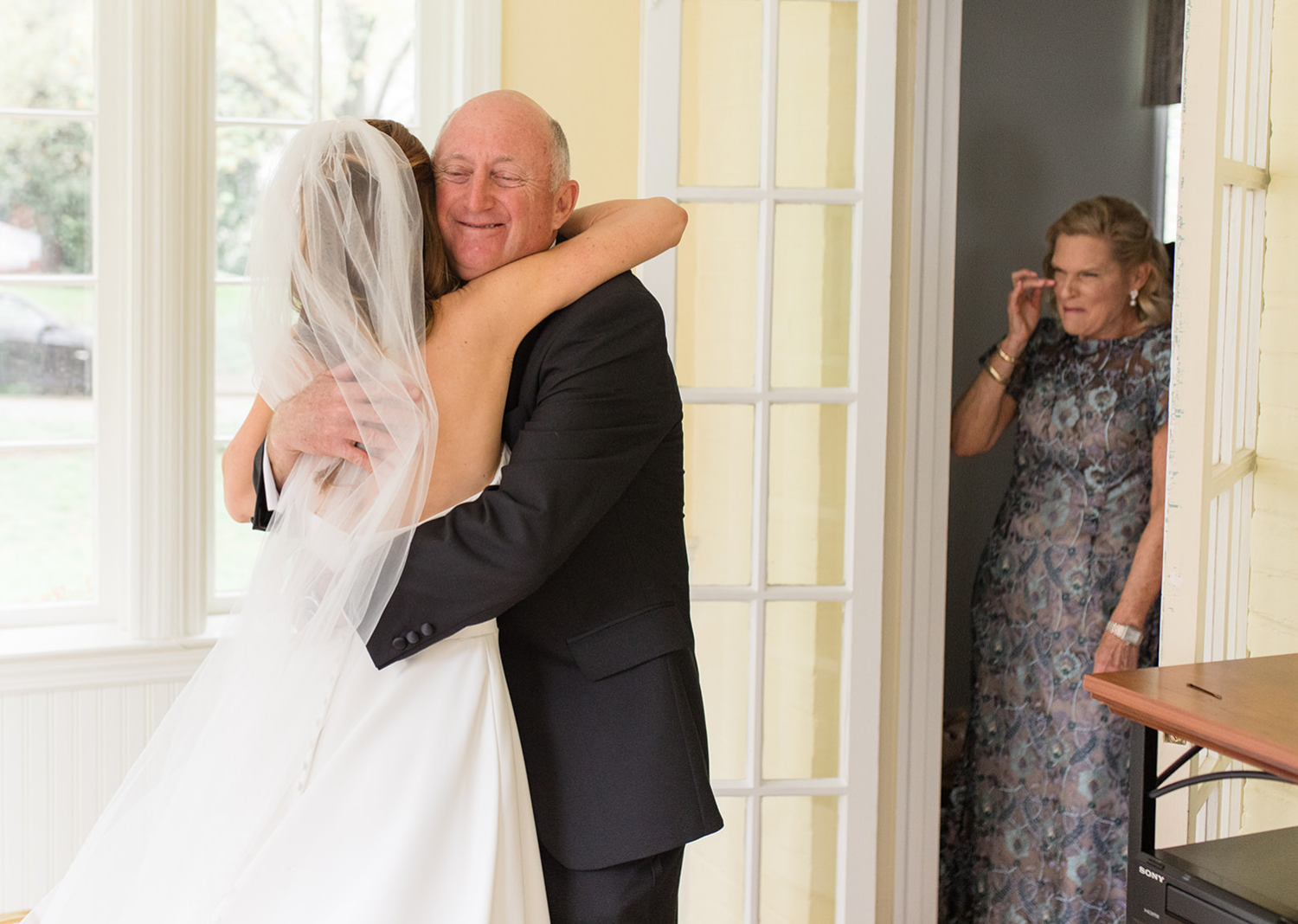 father of the bride and the bride share a hug
