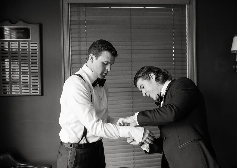 groomsmen helping the groom with his cufflinks
