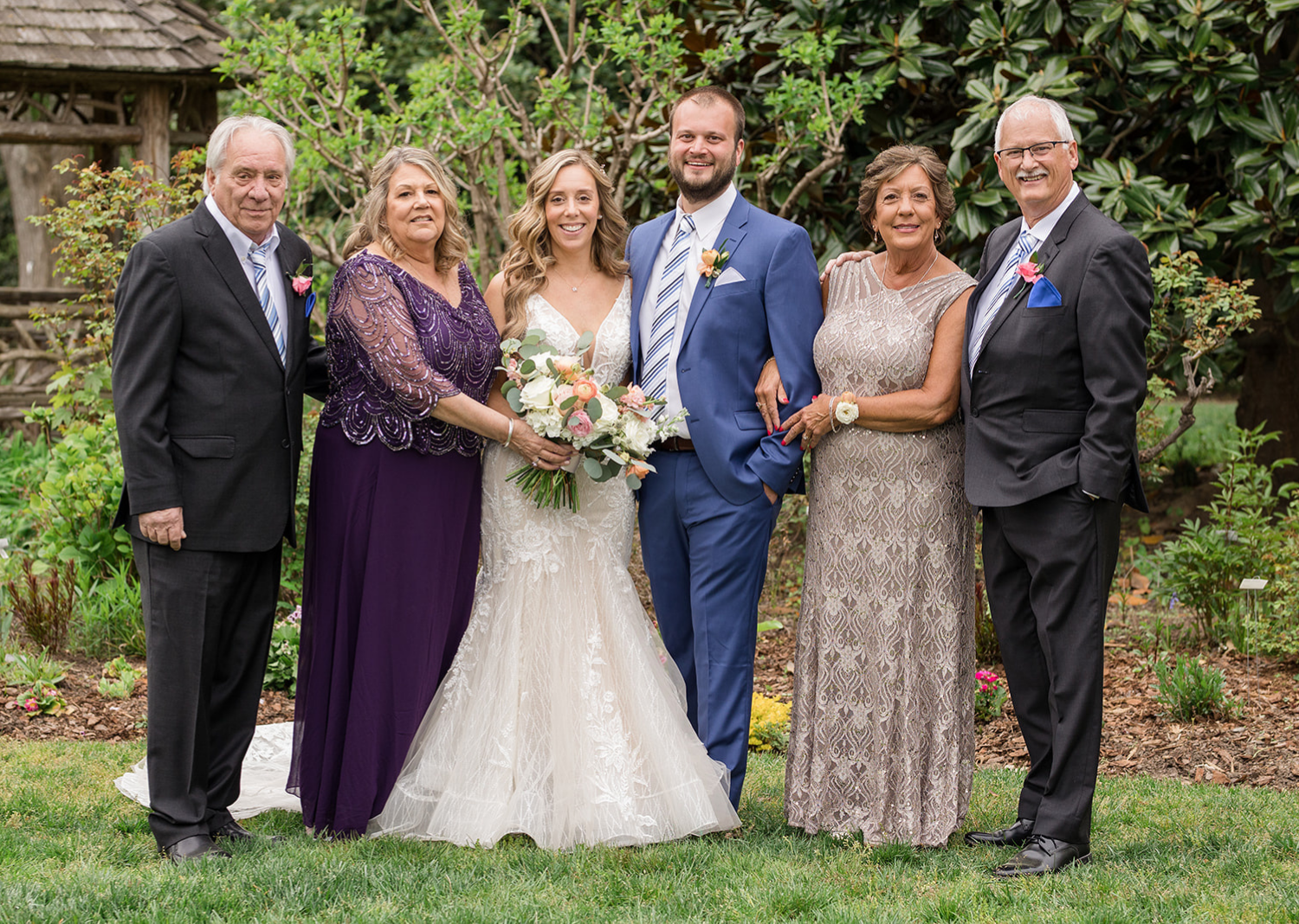 bride and groom with their families for outdoor wedding portraits