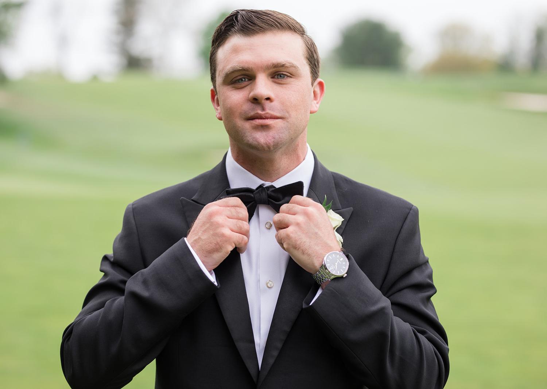 groom fixing his bow tie