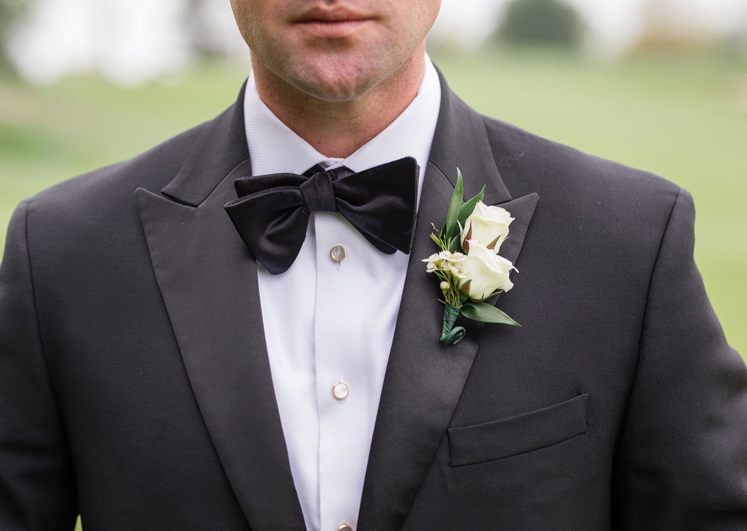 close up shot of the groom's bow tie and boutonniere