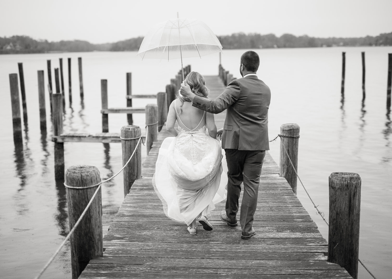black and white portrait of the bride and groom holding the umbrella as it rains