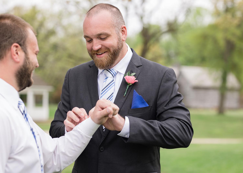 groomsmen helping groom with his cufflinks