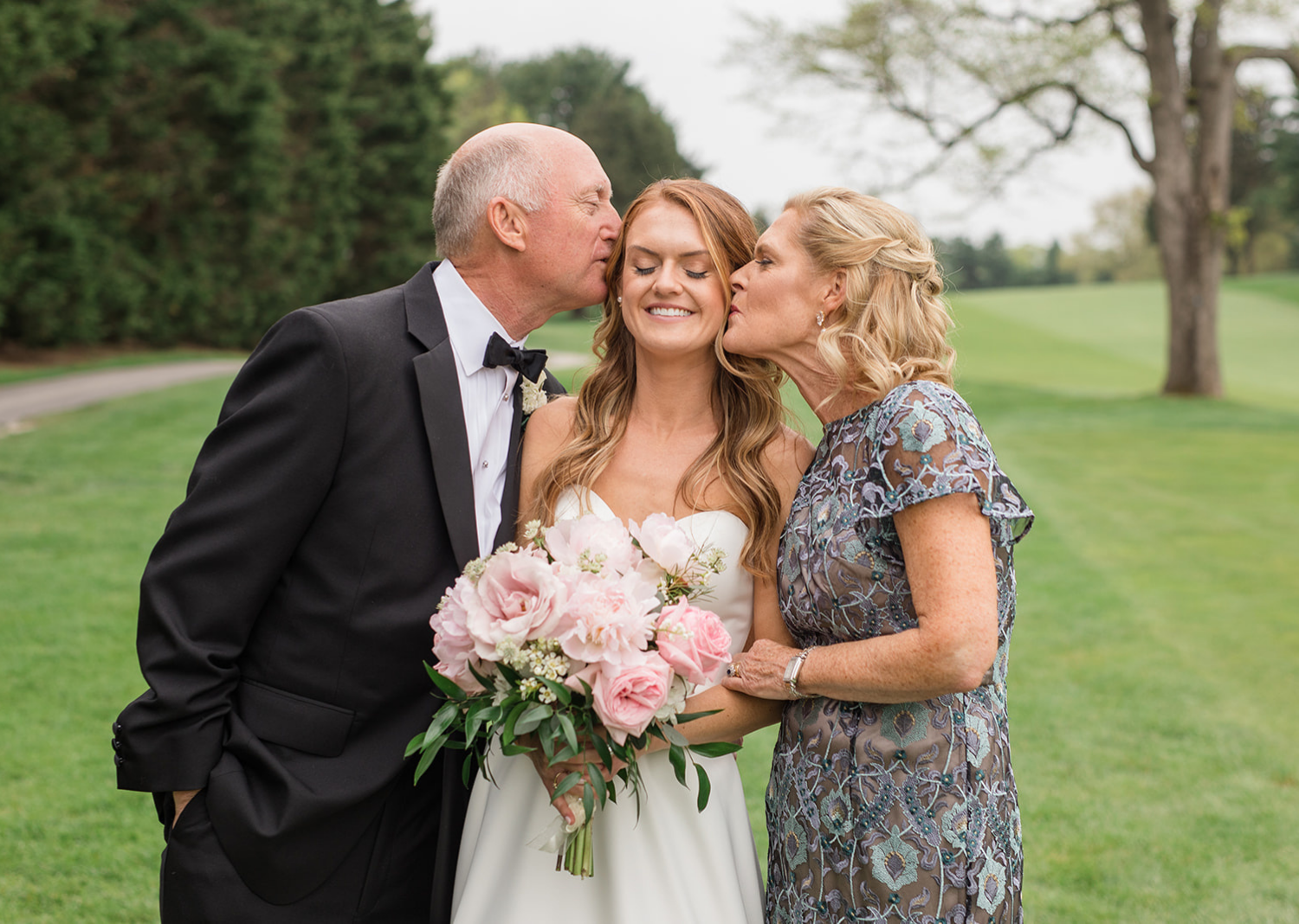 mother and father of the bride give bride a kiss on the cheek