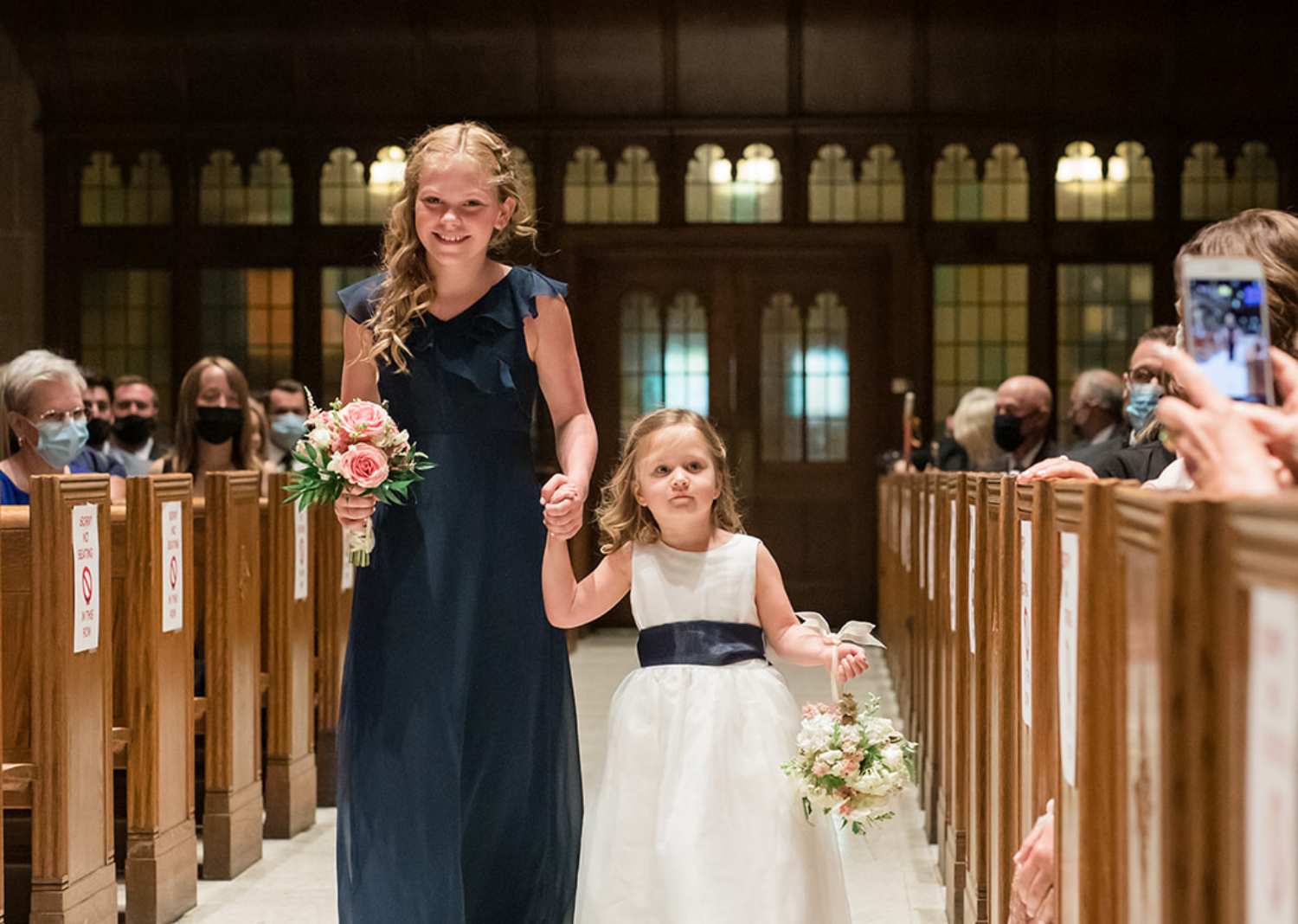 flower girls walking down the aisle of the wedding ceremony