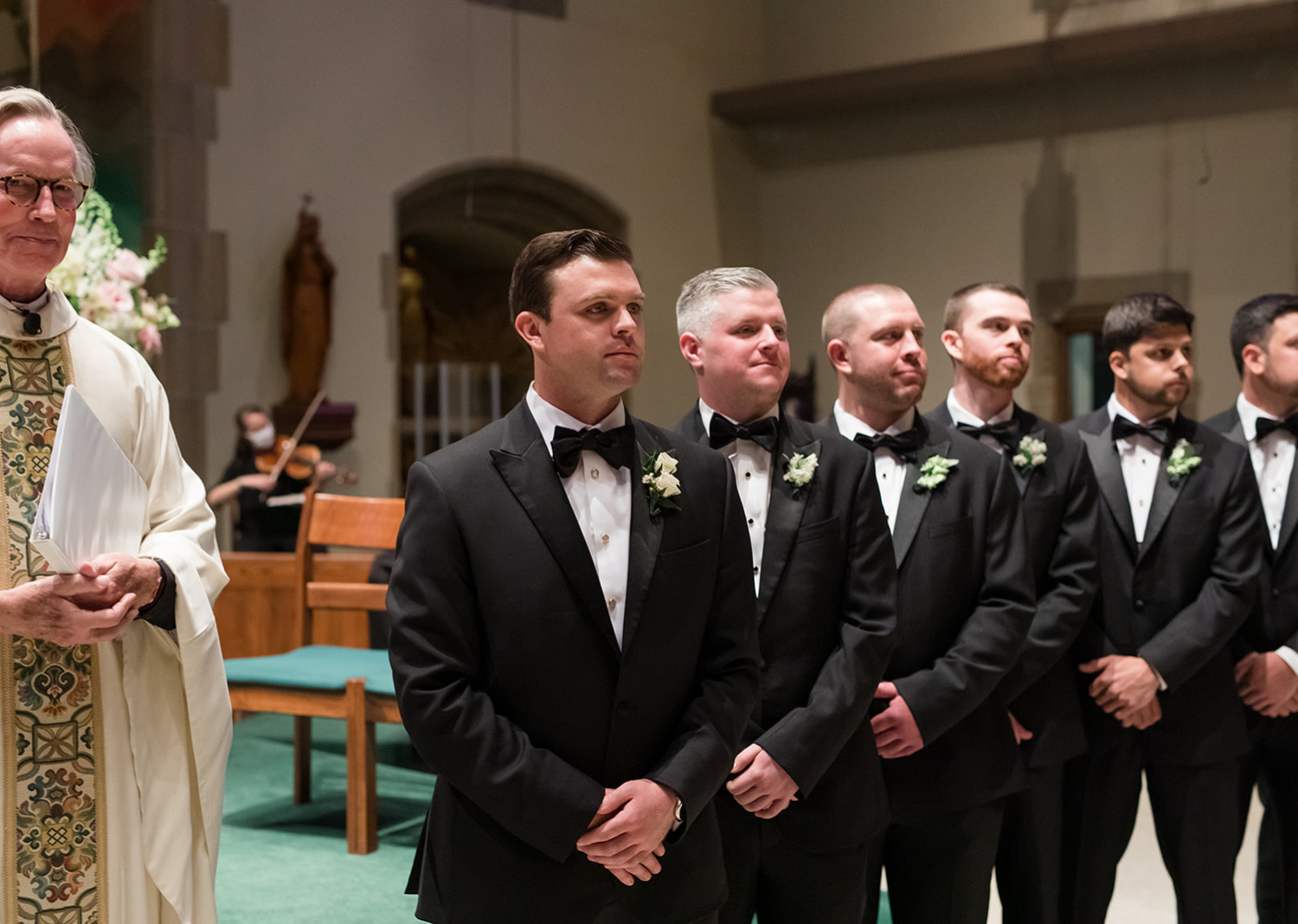 groom standing with his groomsmen waiting at the end of the aisle for his bride