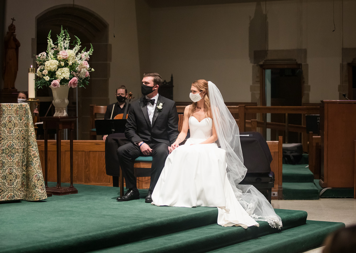 bride and groom sit down at the church for their wedding ceremony as their wearing masks