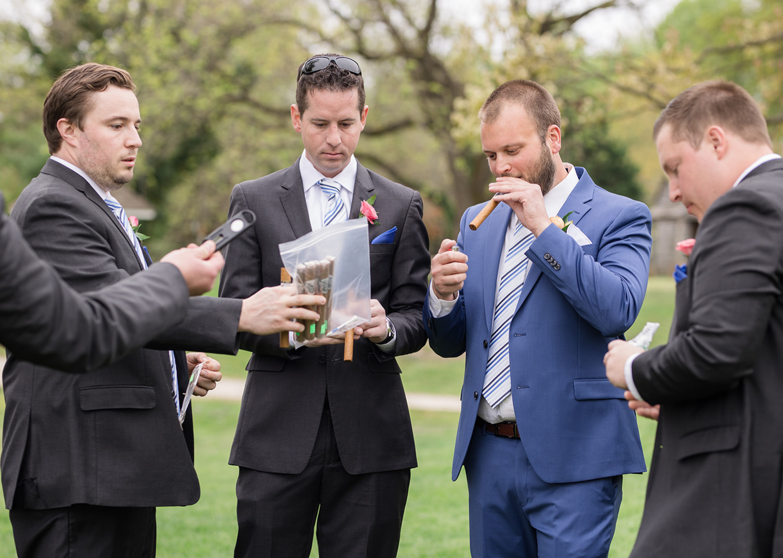 groom and groomsmen smoking cigars before the wedding