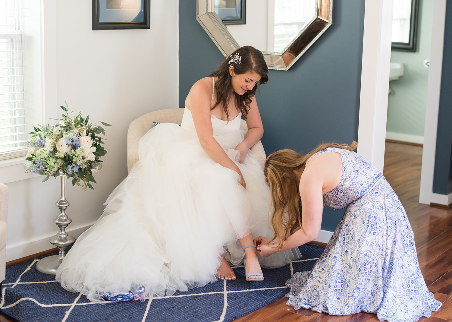 bridesmaid helping the bride put on her shoes