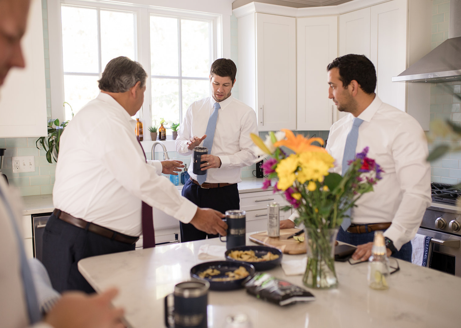 groom and groomsmen sharing a drink in the kitchen area before the wedding day