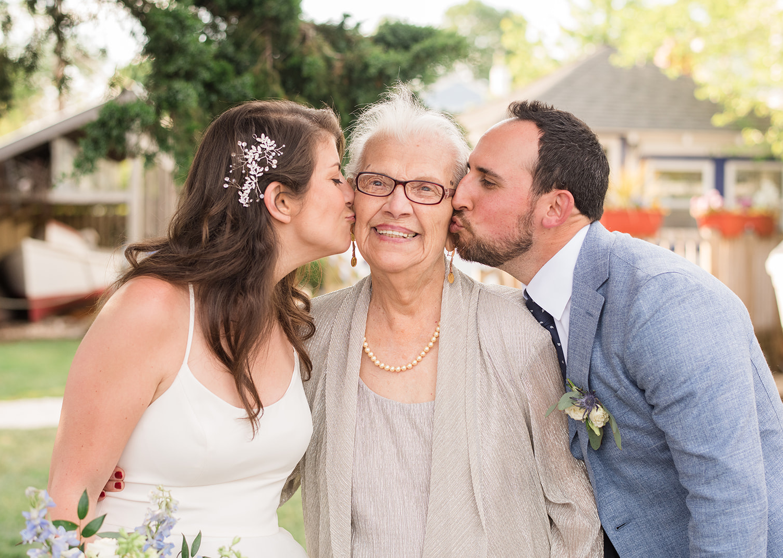 bride and groom both kiss grandma on the cheeks