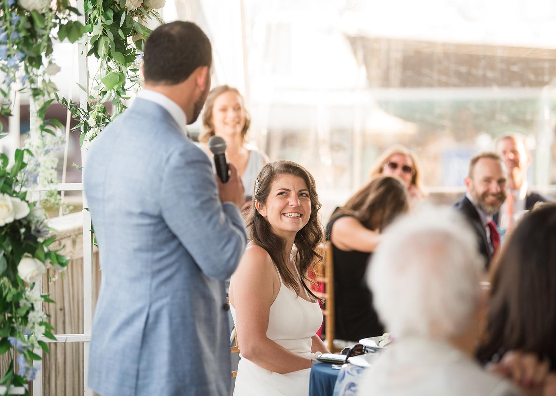 bride smiles as groom gives a speech