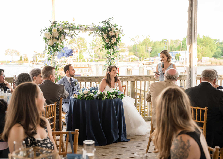 bride and groom smile as bridesmaid gives a wedding speec