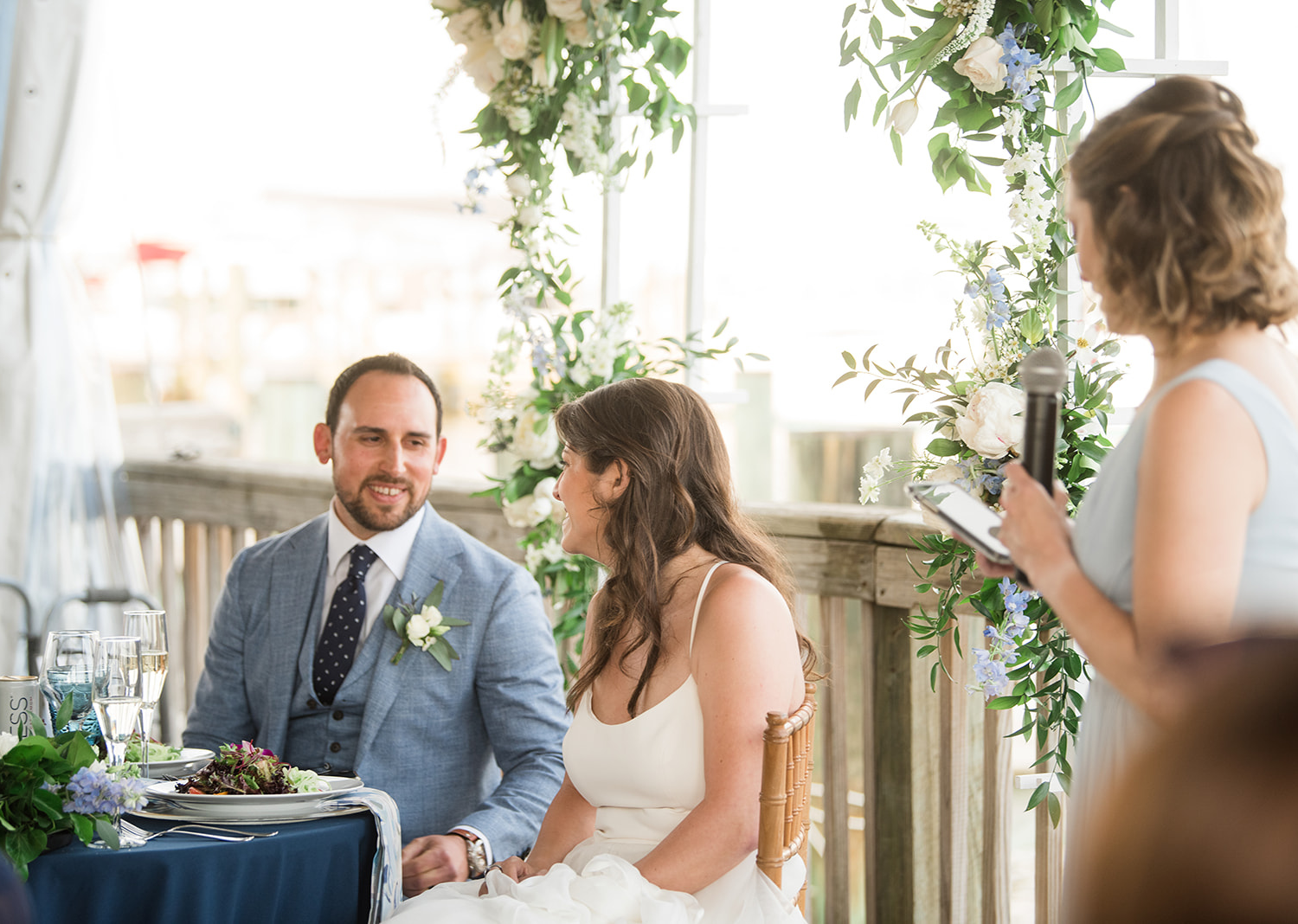 bride and groom smile at eachother as they hear the bridesmaid wedding speech