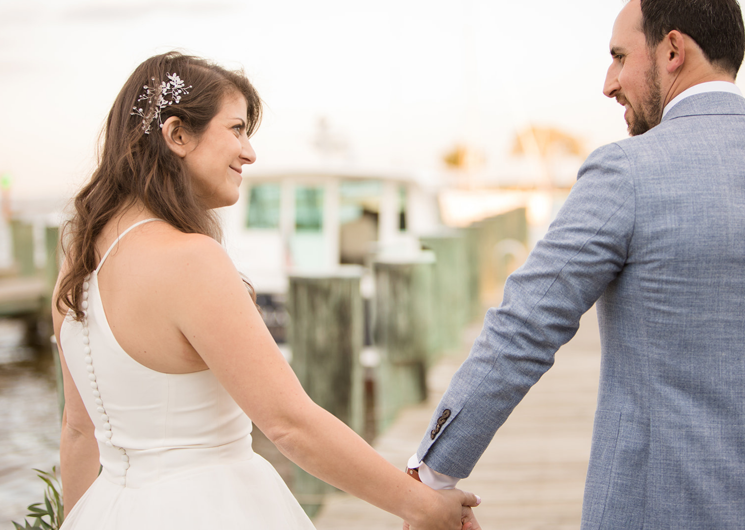 bride and groom smile lookign at eachother as they walk down the pier