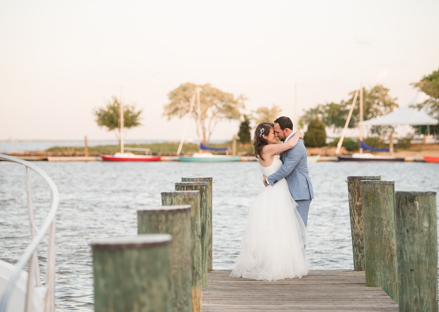 bride and groom share a kiss on the pier