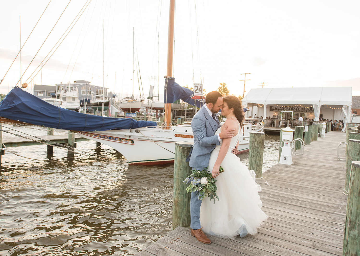 bride and groom share a kiss in the pier in the annapolis maritime museum