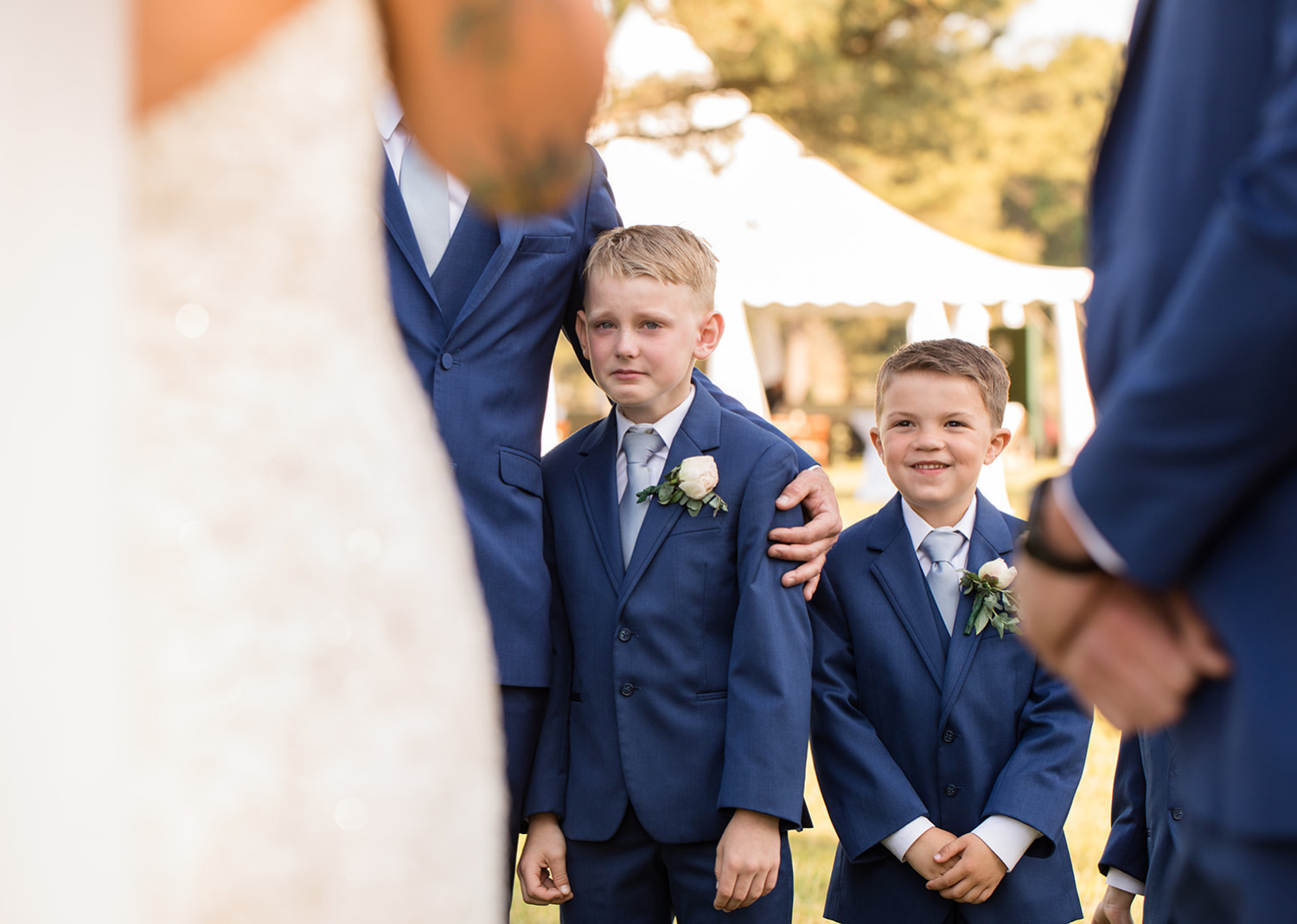 little groomsmen and kids of the bride and groom cry as he hears his aprents read their wedding vows