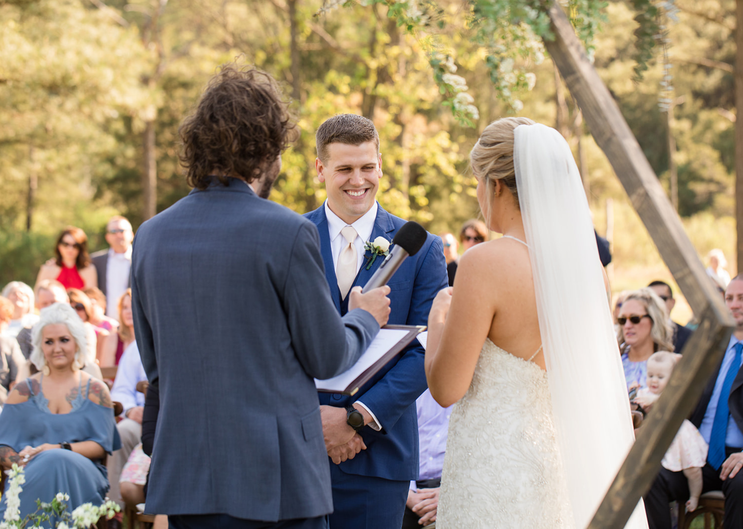 groom smiling as bride reads her wedding vows