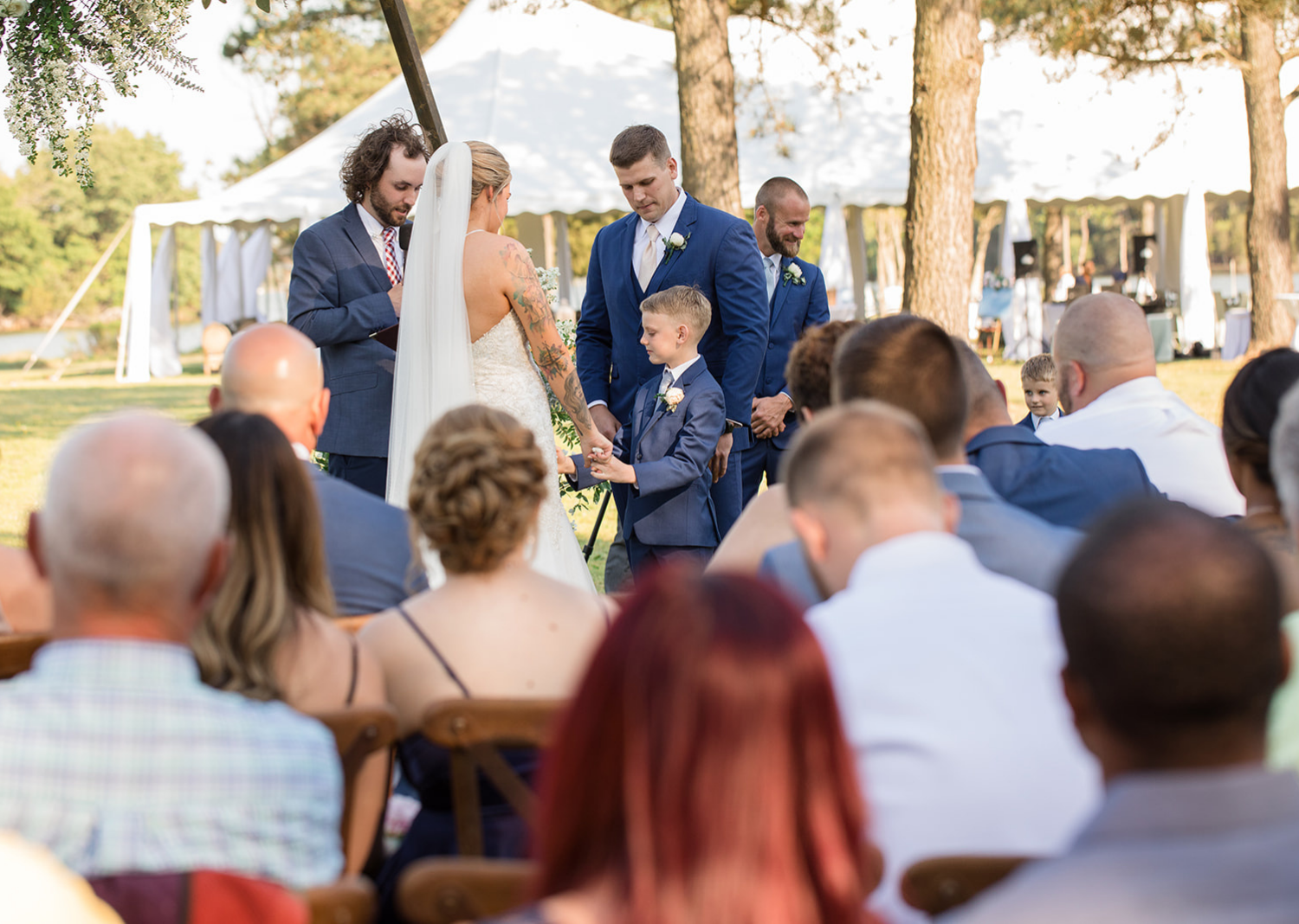 little groomsmen gives bride and groom their wedding rings as a ring bearer