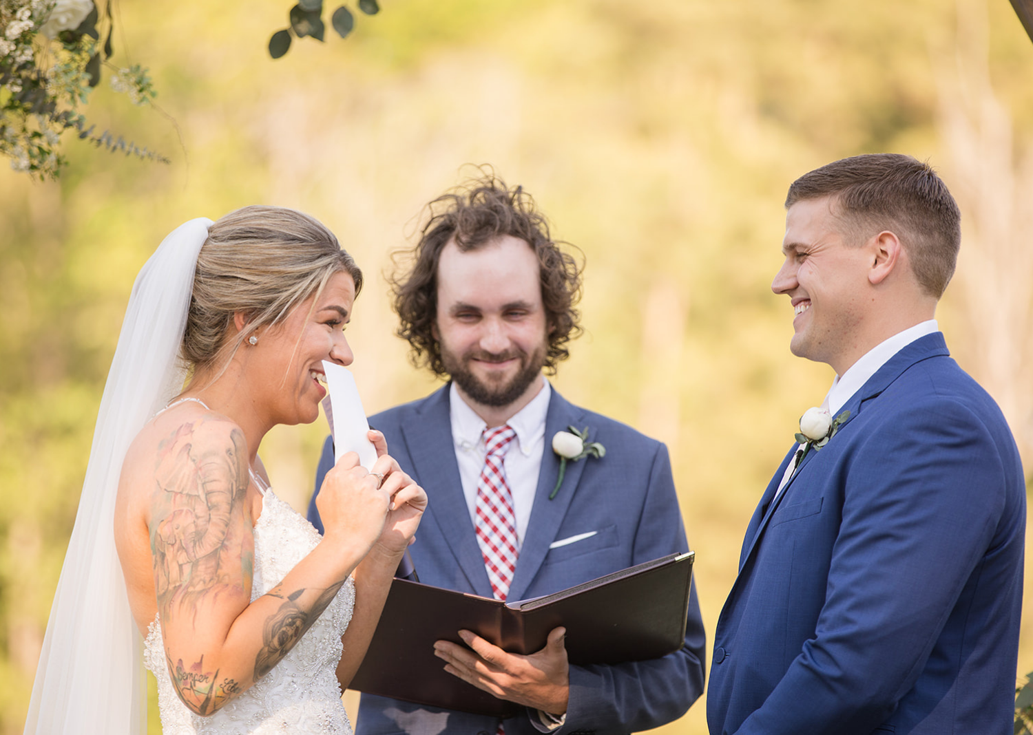 bride smiles as she reads wedding vows to the groom