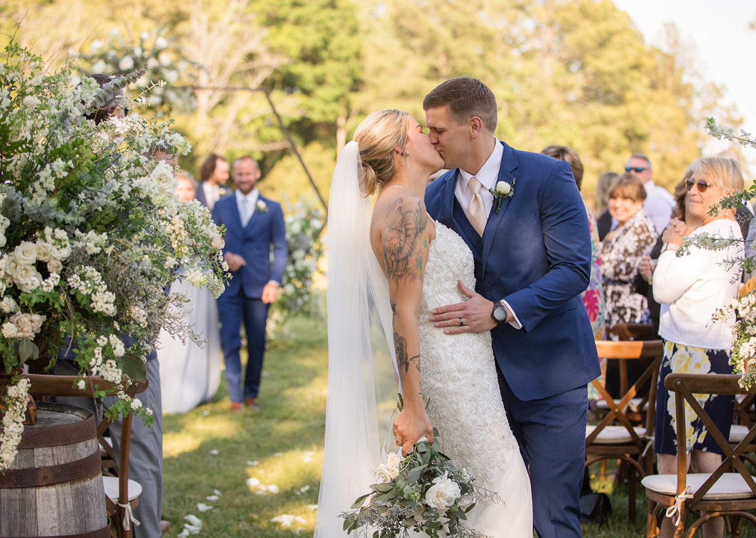 groom kisses bride as they walk down the aisle