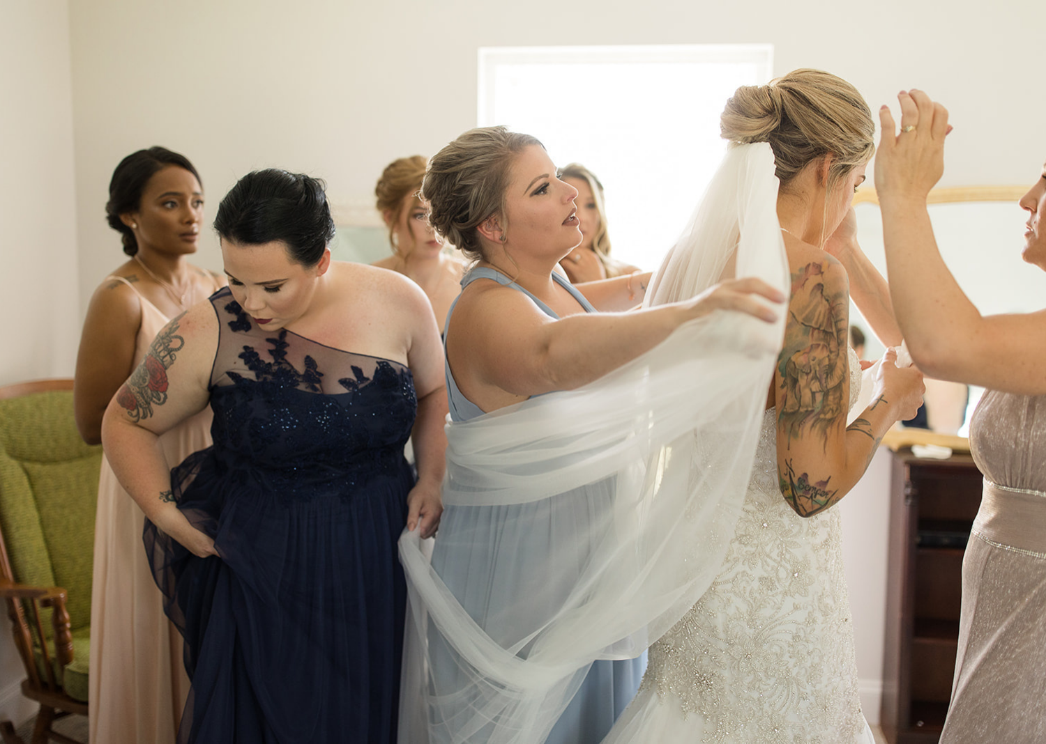 bridal party helping the bride put on her wedding veil