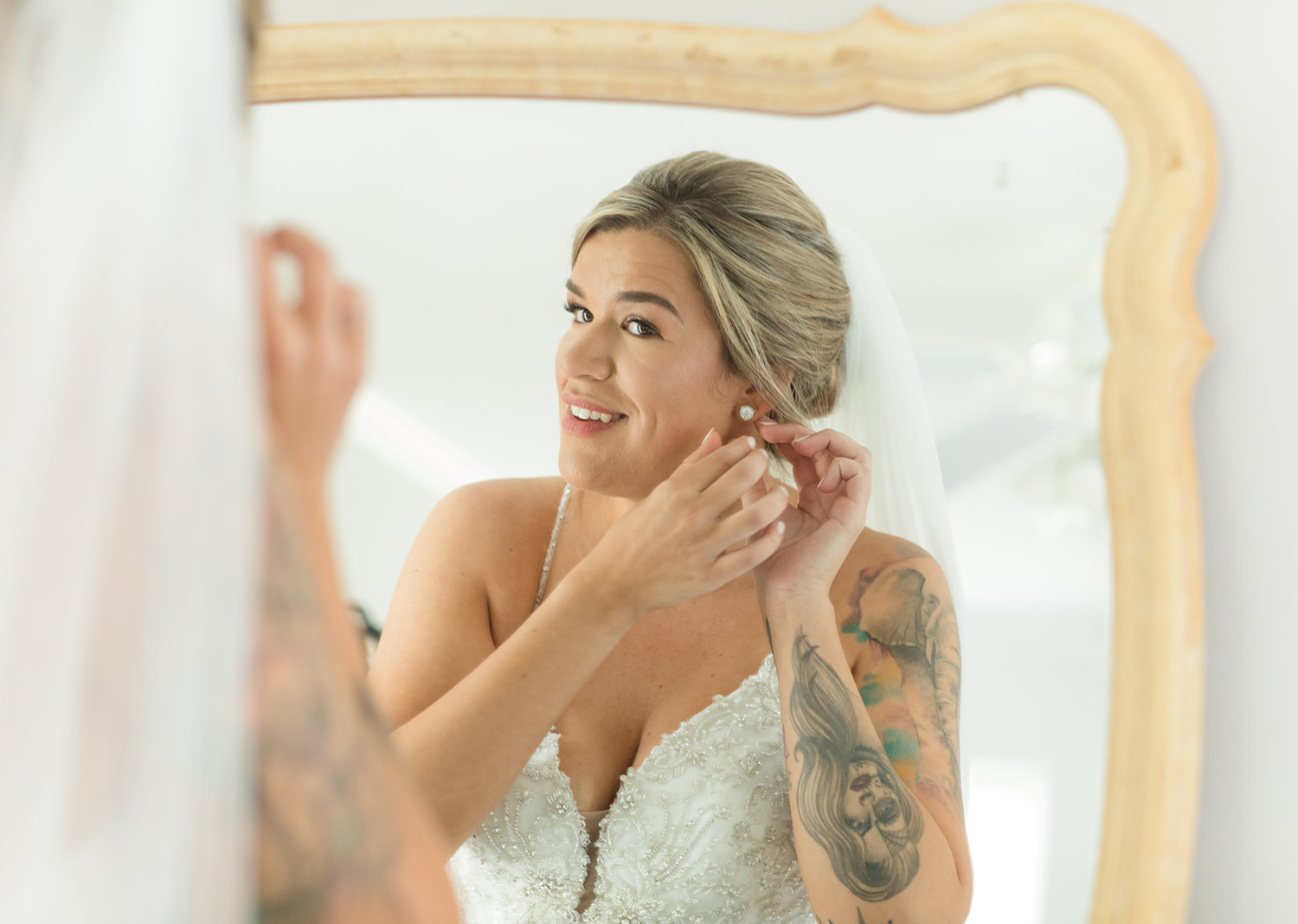bride looking at herself in the mirror while putting on her earrings