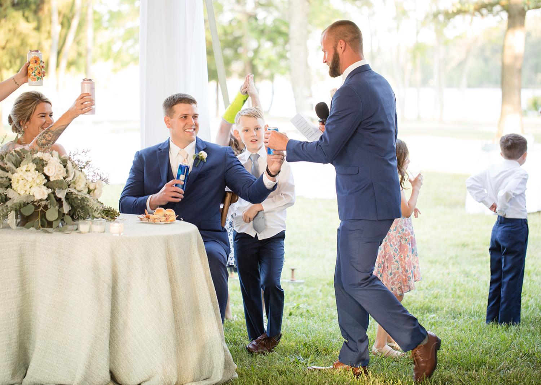 groom and groomsmen toast as groomsmen is giving his wedding speech