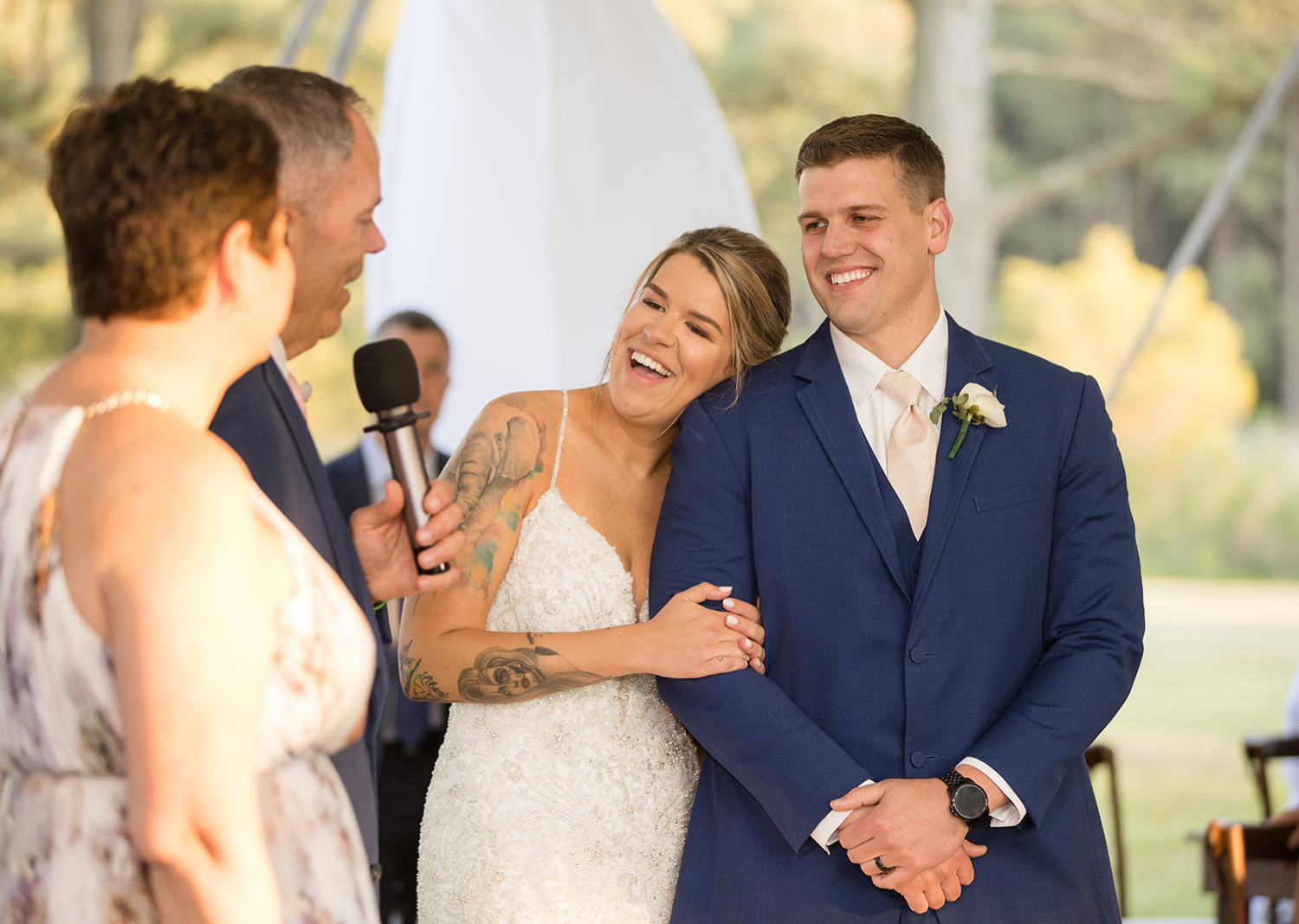 bride and groom smiling as they hear their family giving speeches