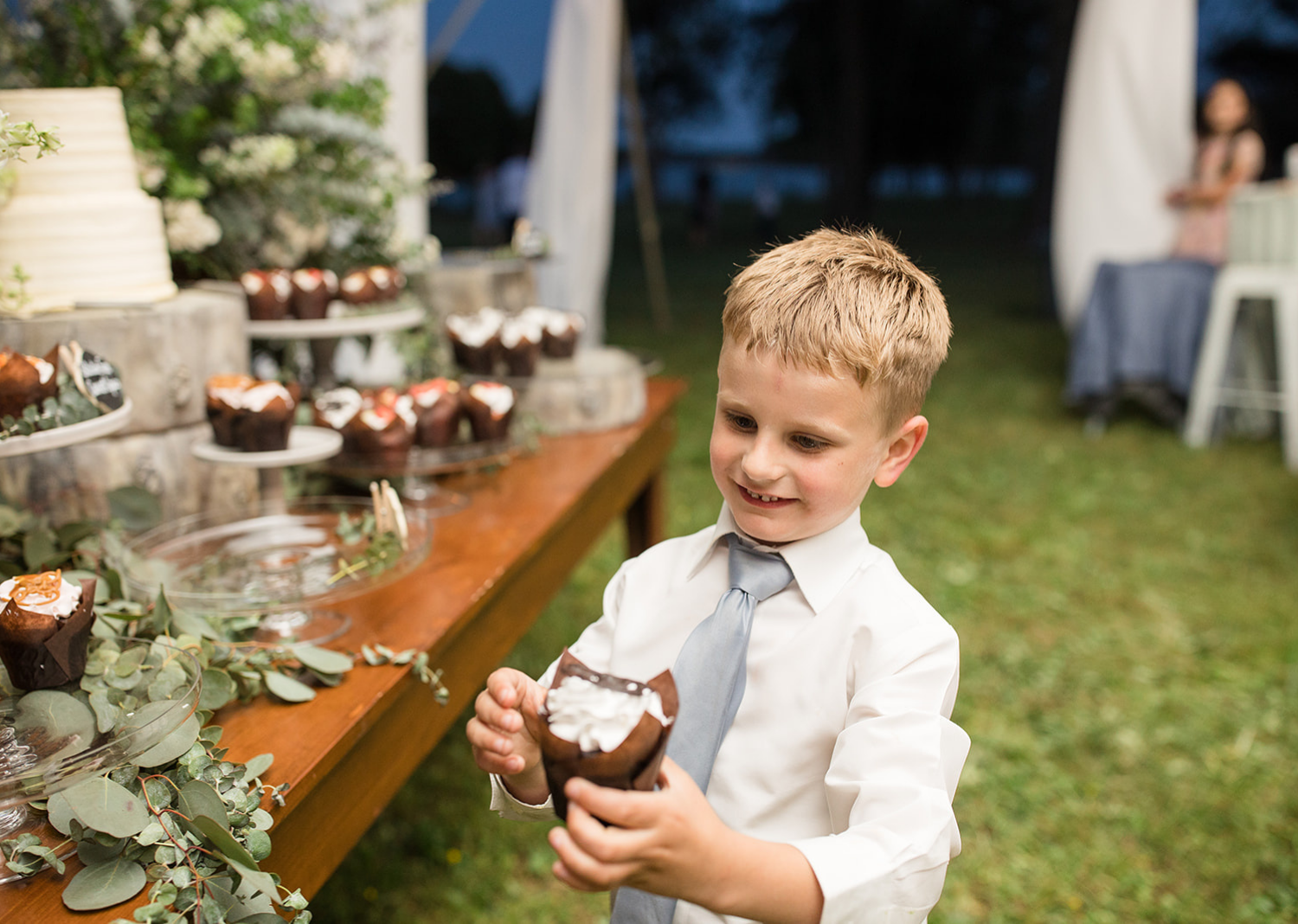 little groomsmen eating a cupcake from the dessert table
