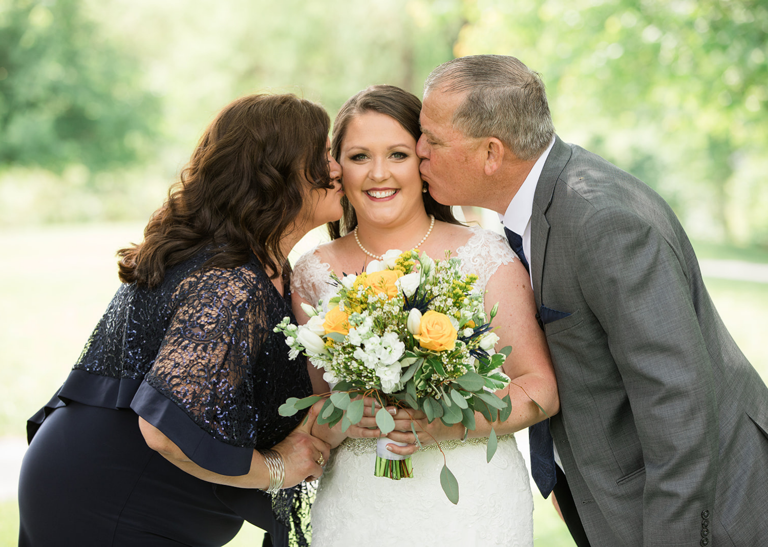 father and mother of the bride kiss her on the cheek