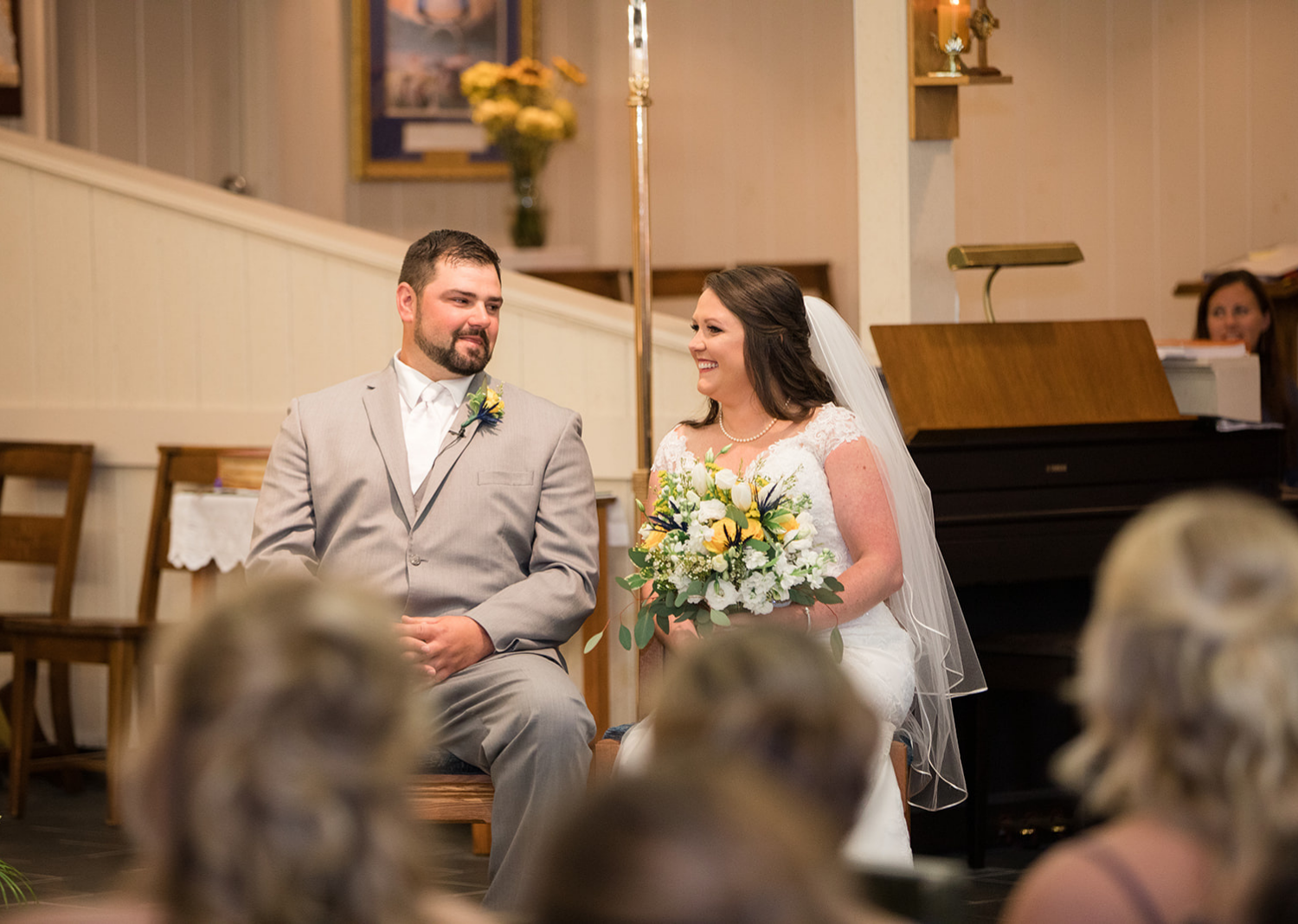 groom and bride smiling as they hear their wedding talk