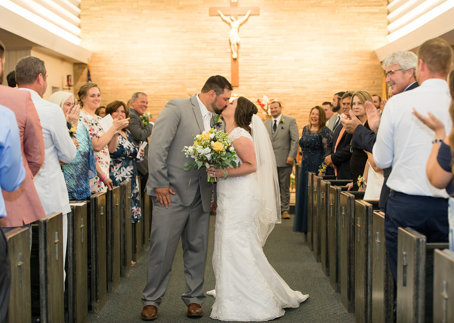 bride and groom share a kiss while walking down the aisle