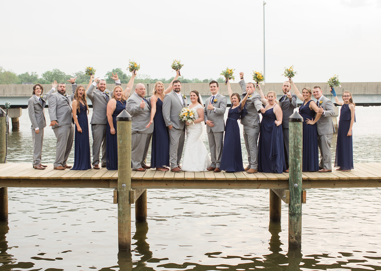 bride and groom with their wedding party on the pier